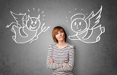 stock photo of hells angels  - Young woman standing between the angel and the devil drawings - JPG