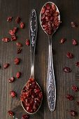 Spice barberry in spoons on wooden background