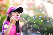 Lovely Little Asian Girl Blowing Soap Bubbles