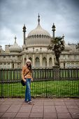 Young woman posing in front of the Brighton Palace Pavilion , a British Royal pleasure palace built in Indo-Saracenic style with ornate onion domes, columns and arches, a popular tourist destination