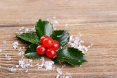 Leaves of mistletoe with berries on wooden background