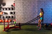 sled rope pull woman pulling weights workout exercise