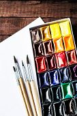 Art Tools - Watercolor Paints And Brushes With Blank White Paper Sheet On Vintage Wooden Background