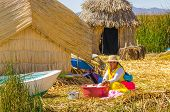 PUNO, PERU, MAY 5, 2014:  Local woman on Uros Islands (Lake Titicaca) washes clothes outdoor