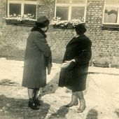 LODZ, POLAND, CIRCA SIXTIES: Two women in fur coats and fur hats talk outdoor in winter, vintage photo