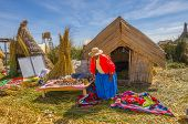 PUNO, PERU, MAY 5, 2014:  Local woman on Uros Islands displays her handmade crafts to sell for tourists