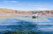 PUNO, PERU, MAY 5, 2014: Boats with tourists head to Uros Islands to visit these floating reed islands