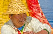 PUNO, PERU, MAY 5, 2014:  Local man, Inhabitant of Uros Islands (Lake Titicaca), rows the traditional reed boat