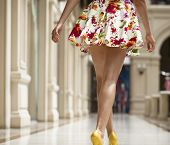 Beautiful shapely female legs back view in flowers dress in the shop