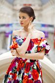 Beautiful young woman in red flowers dress indoor