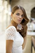 Portrait close up of young beautiful woman in white dress