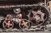 Rusty and dirty tracks and gearwheels of an old Tractor on the Scrapyard