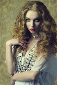 stock photo of jewelry  - Lovely sensual woman wearing antique clothes and jewelry and posing with long curly hair - JPG