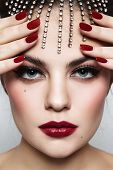 Close-up portrait of young beautiful woman with stylish make-up and manicure