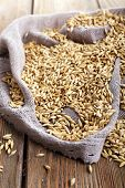 Oat on sackcloth on wooden background