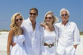 Four people, two seniors, couples or family generations, wearing white clothes together having fun on vacation on a tropical beach