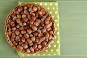 Hazelnuts on wicker mat on wooden background