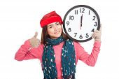 Asian Girl Show Thumbs Up With Red Christmas Hat And Clock At Midnight