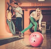 Blond smiling girl throwing ball in a bowling club
