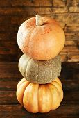 Ripe different pumpkins on wooden background