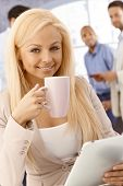 Closeup portrait of attractive young blonde businesswoman drinking tea, using tablet, smiling at camera.