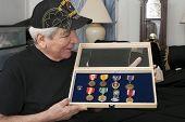 Vietnam Vet Looks Over His Medals