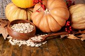 Pumpkins and seeds in bowl on wooden background