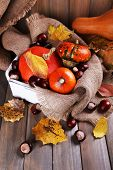 Pumpkins in box on sackcloth on wooden background