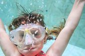 child girl swimming underwater in mask