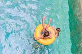 Swimming, summer vacation - lovely child boy and girl playing in blue water (space for text)