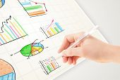 Business person drawing colorful graphs and icons on plain paper