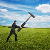 angry screaming businessman holding big hammer. photo at outdoor
