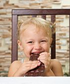 Little smiling girl with chocolate at light room