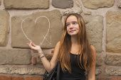Teen girl in frustration standing against the wall with the drawn heart. Broken love concept.