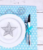 White plate, fork, knife and Christmas decoration on polka dot napkin on wooden background