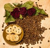 dry red roses and cookies on coffee seeds and wooden background