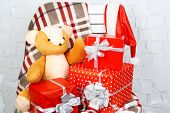 Christmas presents on blanket on white chair on brick wall background