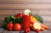 Tomato juice in glass and fresh vegetables on wooden table on wooden wall background
