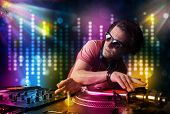 Young Dj playing songs in a disco with light show