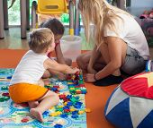Doing puzzle with tutor in nursery