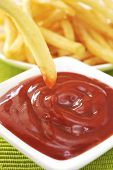 French fries and tomato ketchup in white dish. Fried potatoes