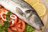 stock photo of bass fish  - Freshly Bass Fish with vegetables on wooden cutting board - JPG