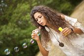 Beautiful woman in the park playing in bubbles cup