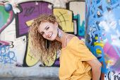 Teenage hip blond girl standing by graffiti wall