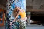 Teenage hip blond girl standing in front of graffiti wall