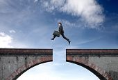 picture of gap  - Businessman jumping over the gap between two parts of a bridge - JPG