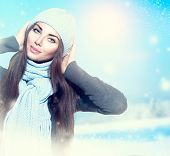 Beauty Winter Girl wearing hat and scarf. Happy Winter holiday woman outdoor portrait