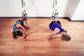 Two Women Working Out With Straps In Gym