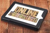 online education - text in letterpress wood type on a digital tablet against red barn wood