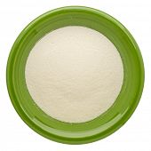 collagen protein powder on an isolated green ceramic bowl, top view